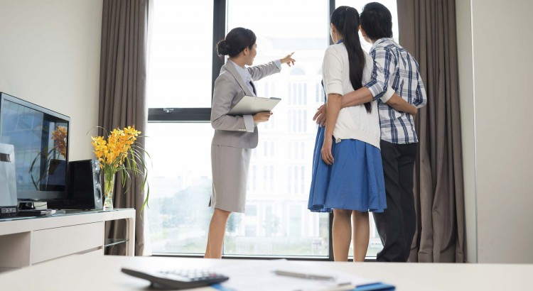 Estate broker showing married couple the view from the apartment window