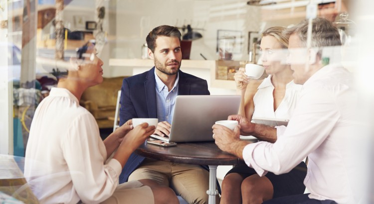 A real estate agent meets with prospective clients in a cafe