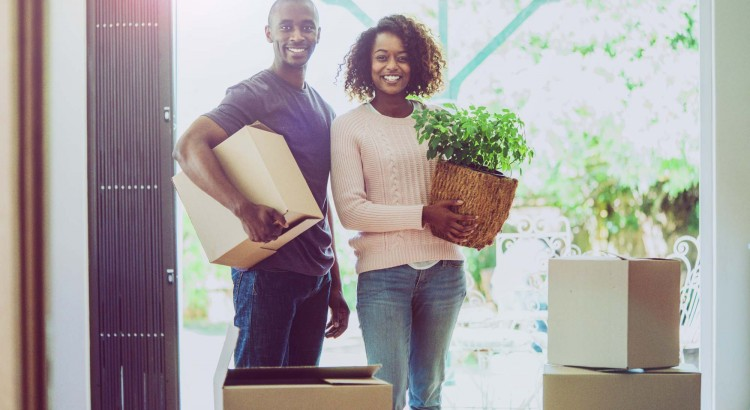 A photo of young couple with cardboard boxes and potted plant. Portrait of man and woman are moving house. They are smiling while standing at entrance of home.